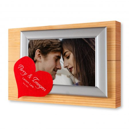 Photo frames and handmade hearts over wooden background