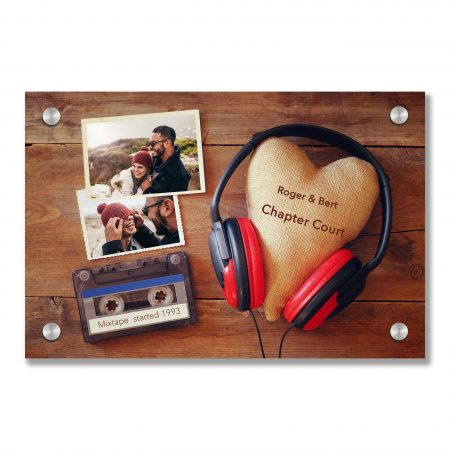 Top view of headphones with fabric heart next to photo frames